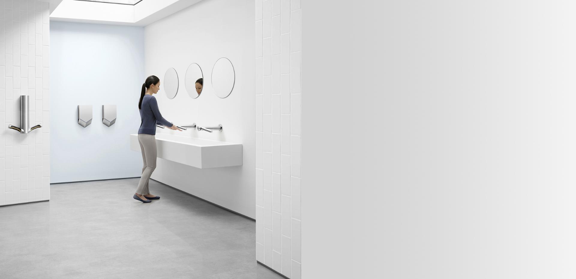 ผู้หญิงกำลังล้างมือด้วยเครื่องเป่ามือ Dyson Airblade Wash+Dry