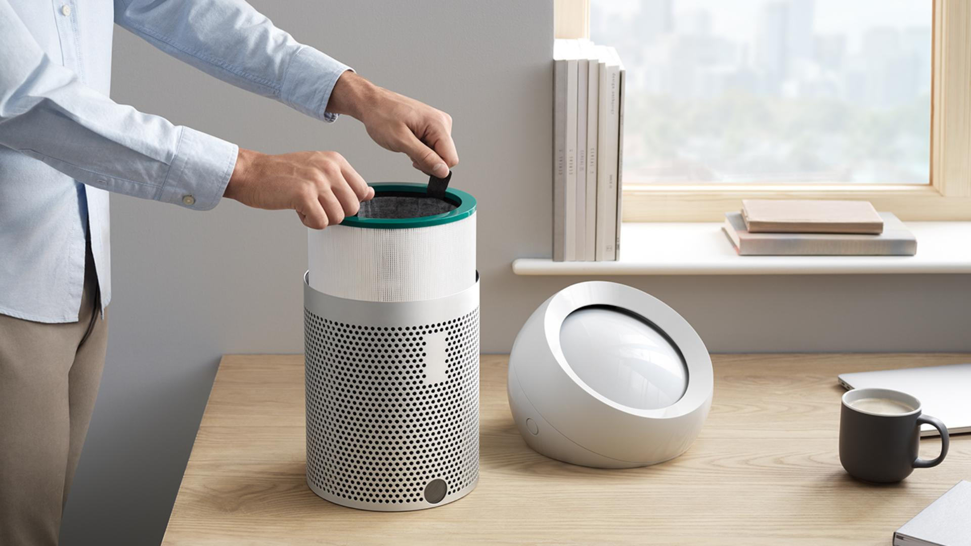 A user changing the filters on the Dyson Pure Cool Me personal purifier fan