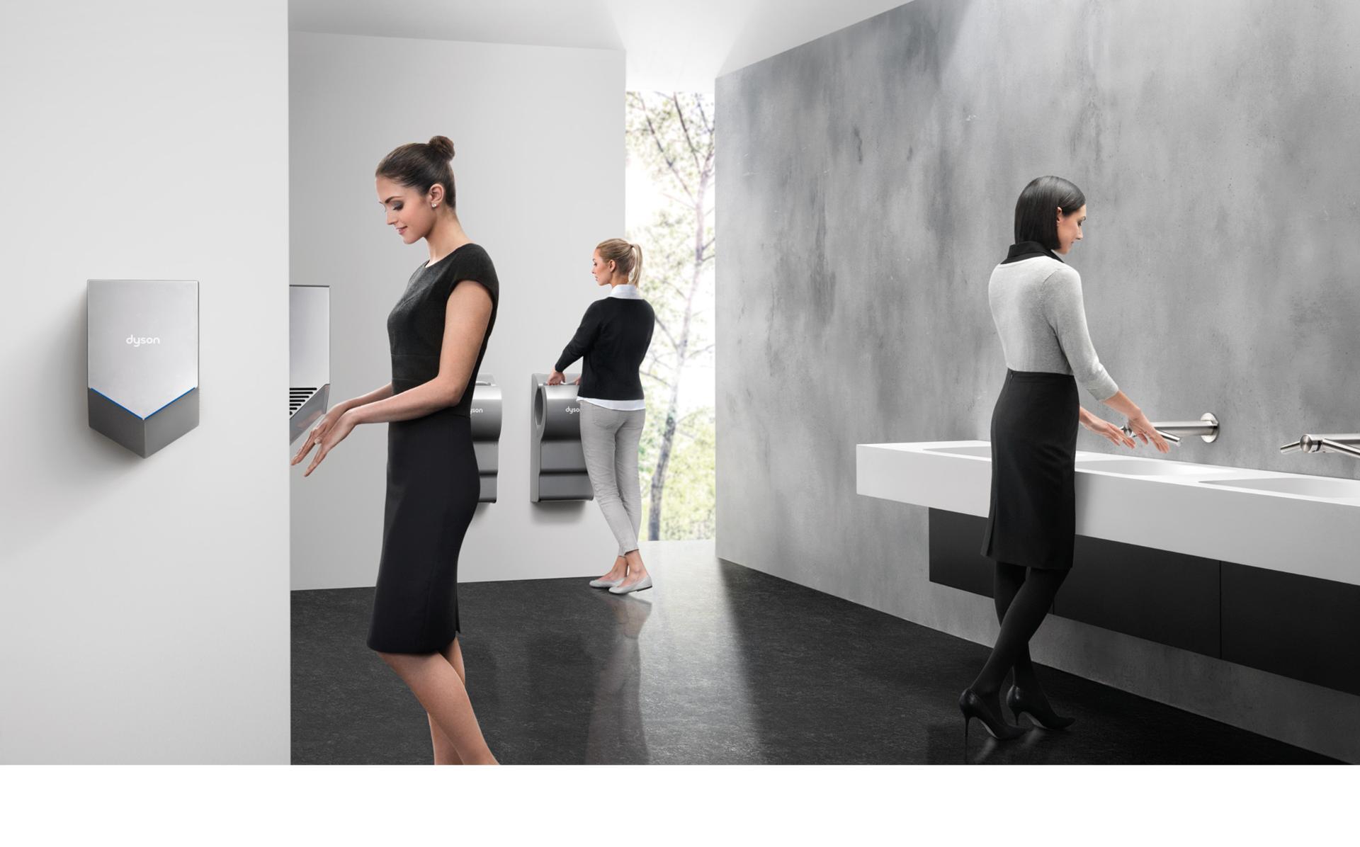 Dyson Airblade el kurutma makinesi kullanarak ellerini kurutan kadınlar