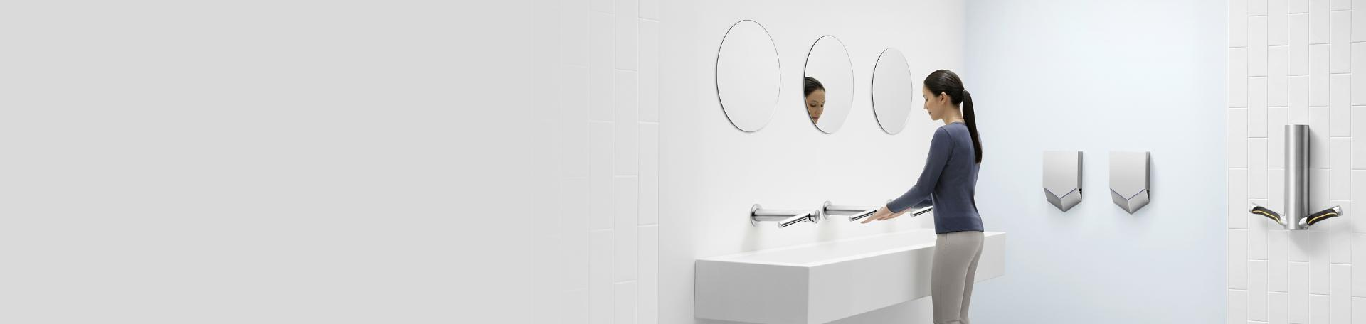 Woman using Airblade technology in bathroom setting
