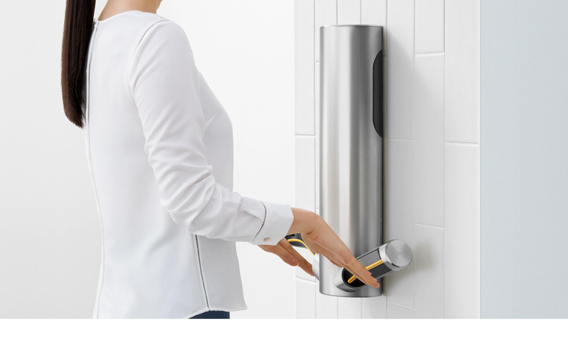 Woman drying hands at Dyson Airblade 9kJ