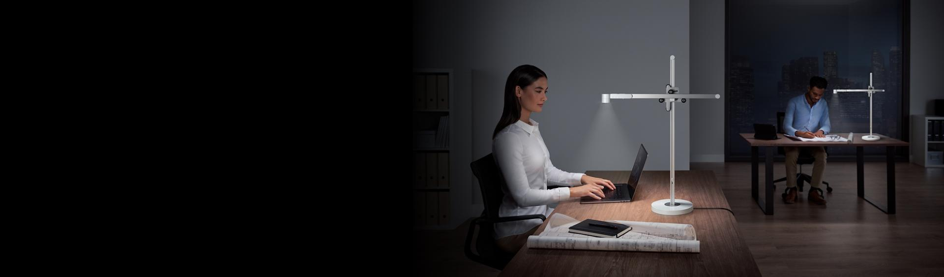 Two people at work using Dyson Lightcycle desk lights