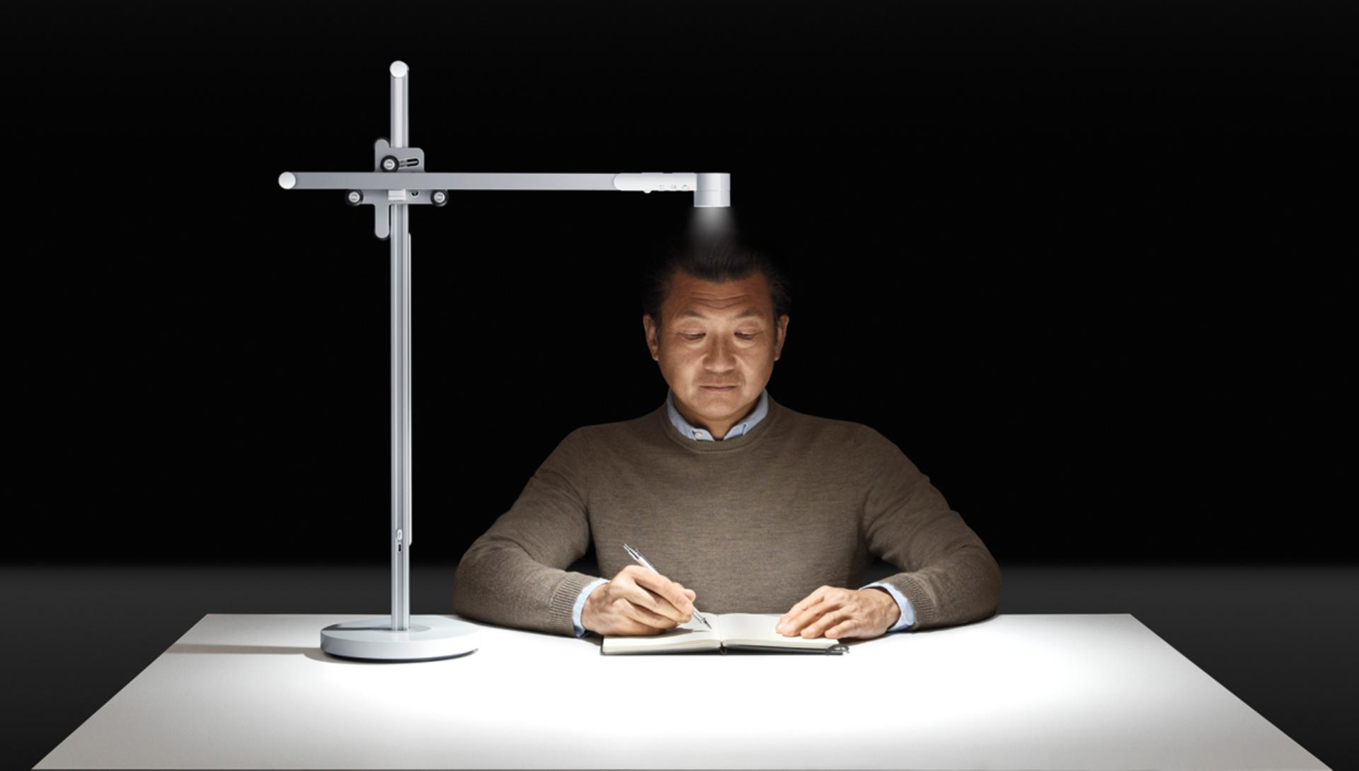 Older model using Dyson Lightcycle light at his desk to work