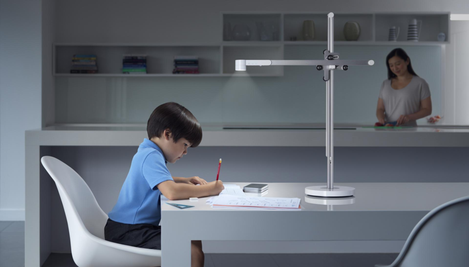 Child working at a table under light from the Dyson Lightcycle desk light