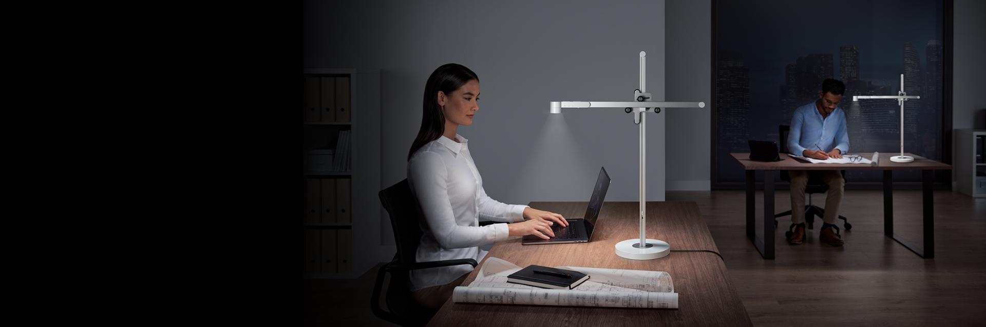 شخصان يستخدمان وحدة الإضاءة المكتبية Dyson Lightcycle في العمل