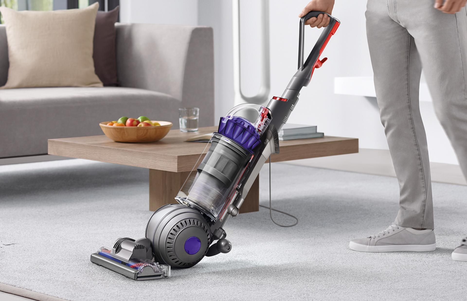 A man vacuuming floor using the Dyson upright vacuum cleaner