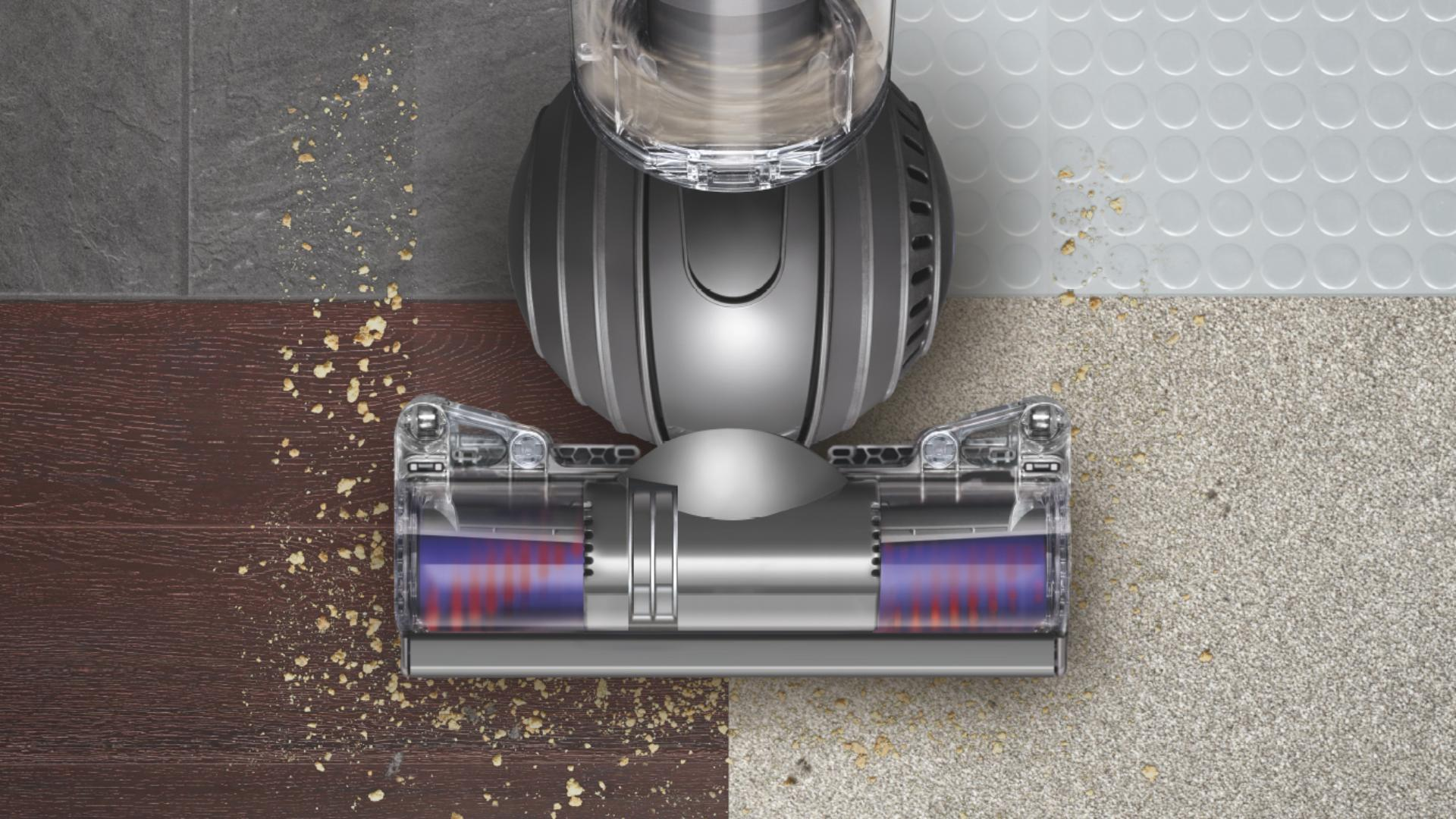 Vacuum cleaner head picking up debris from four different intersecting floor types.