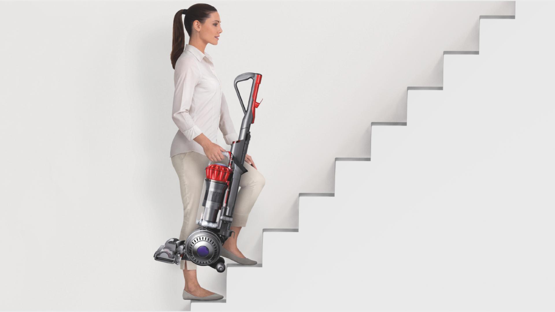 Woman carrying an upright vacuum up a set of stairs.