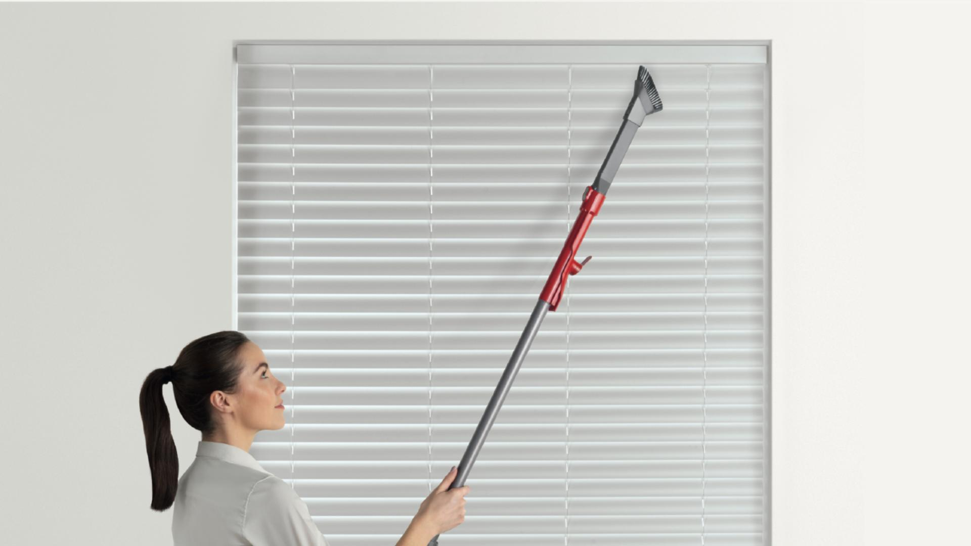 Woman using vacuum wand to clean the top of a blind that's otherwise out of reach.