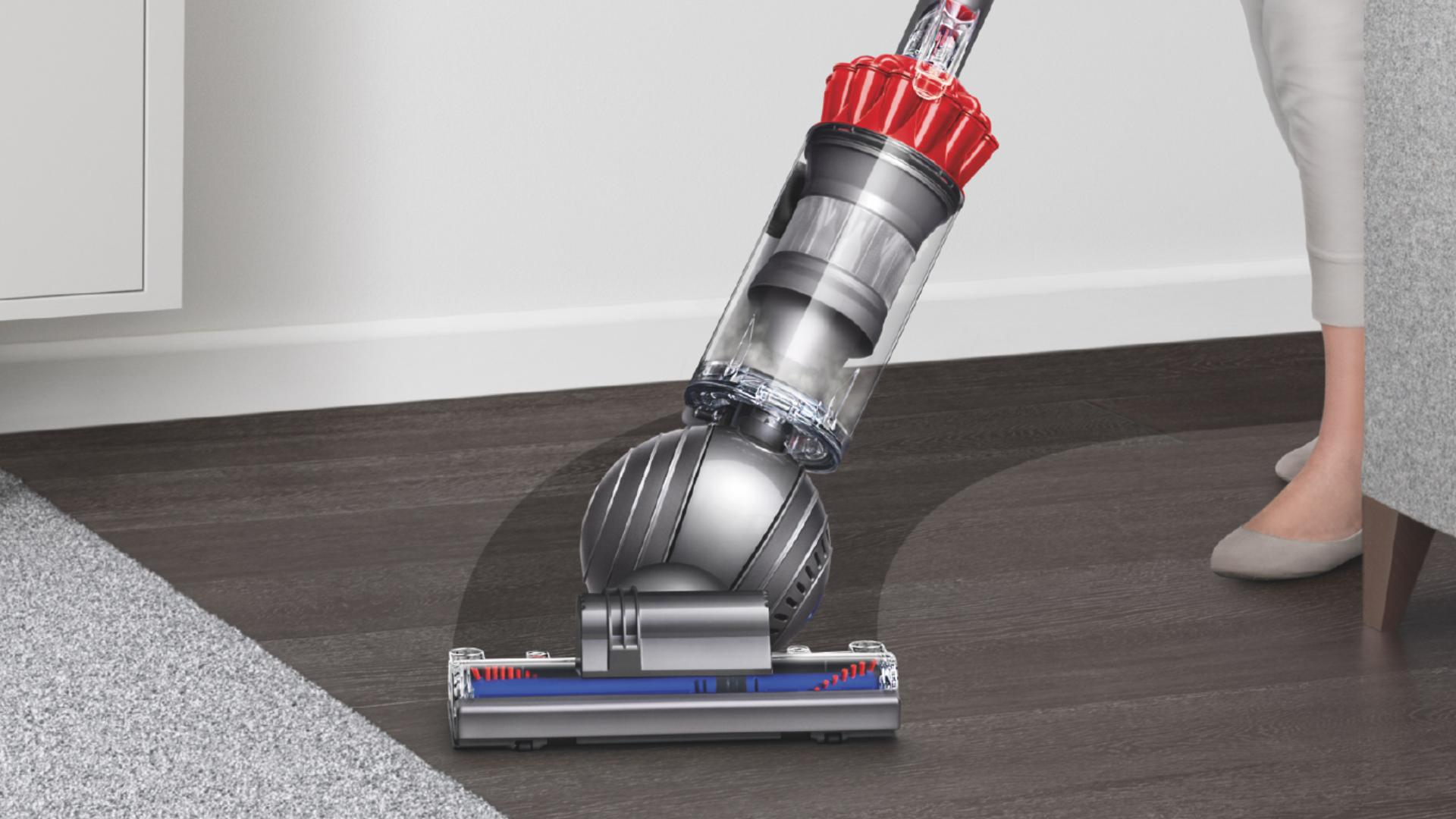 Upright vacuum cleaner being steered in a sweeping arc across a black hard floor surface.