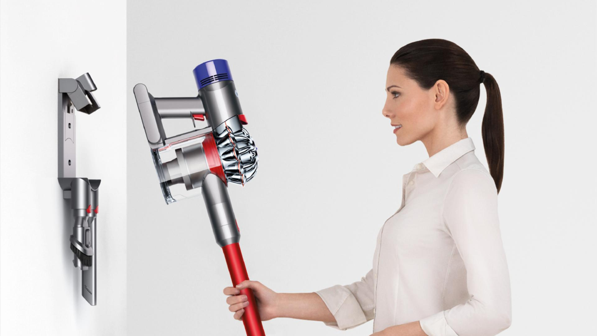 Woman placing Dyson V7 vacuum back ino storage dock