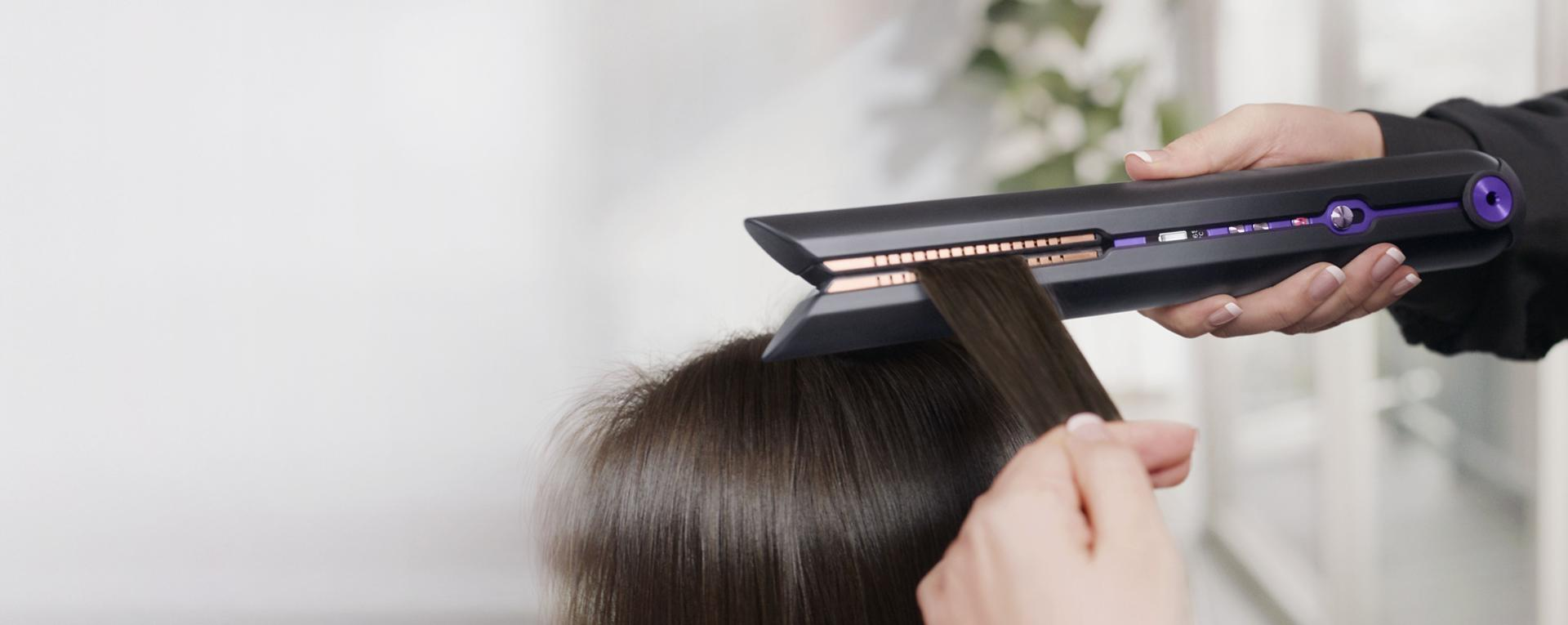 A stylist using the Dyson Corrale™ straightener Professional