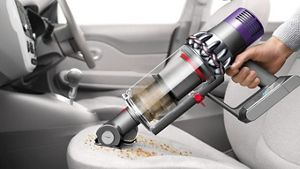 Dyson Cyclone V10™ vacuum in handheld mode cleaning car seat