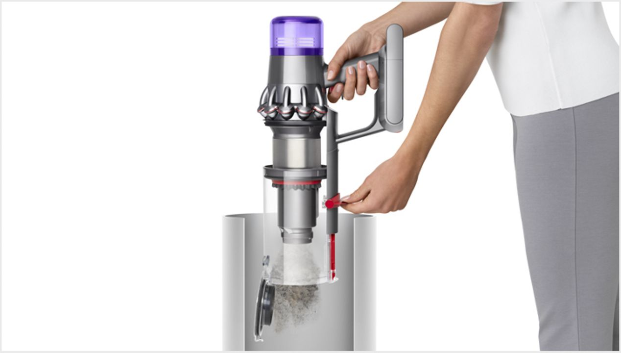 Woman emptying Dyson V11 vacuum into bin