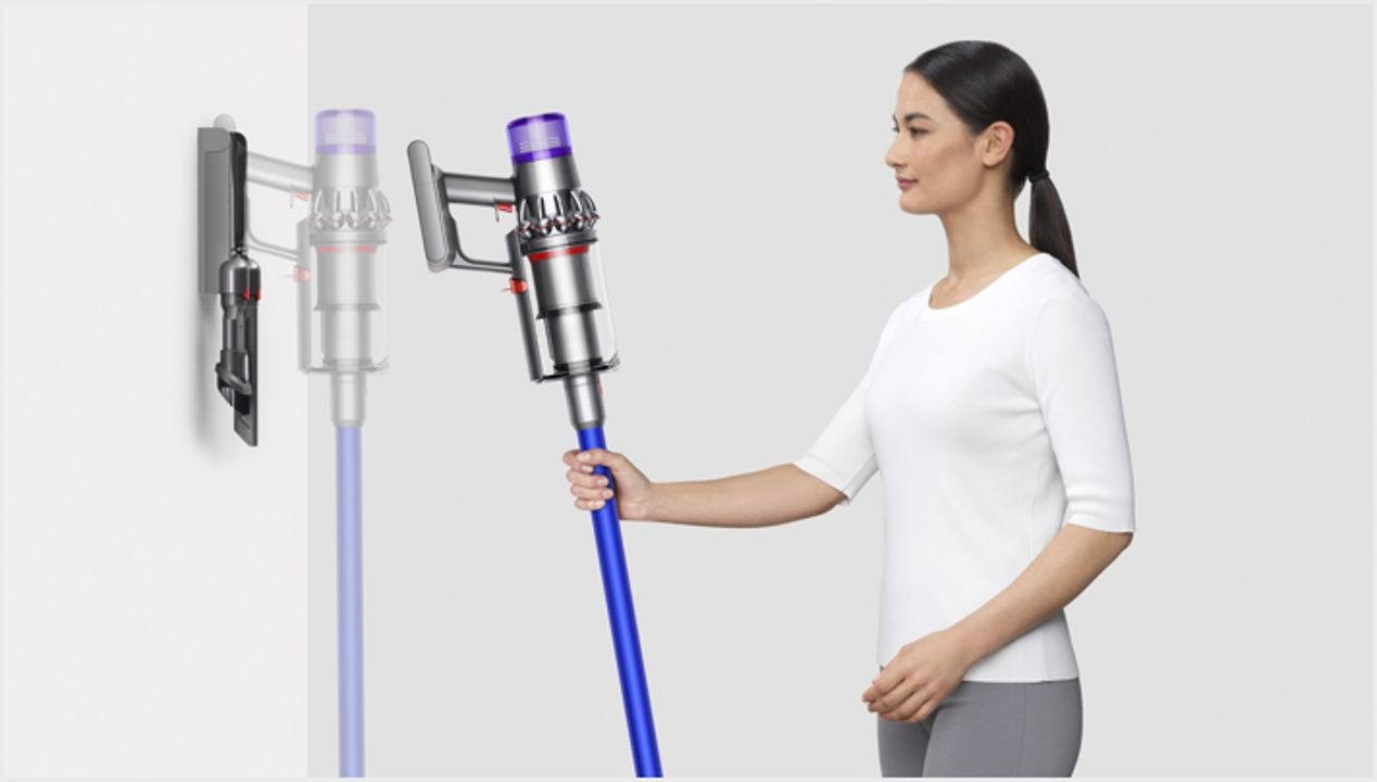 Woman placing Dyson V11 vacuum into wall charging dock