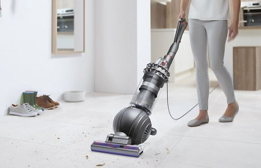 Woman Vacuuming Floor Using The Dyson Upright Vacuum Cleaner