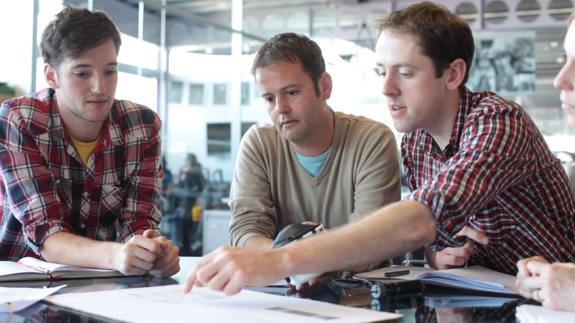 Three engineers working with notepads