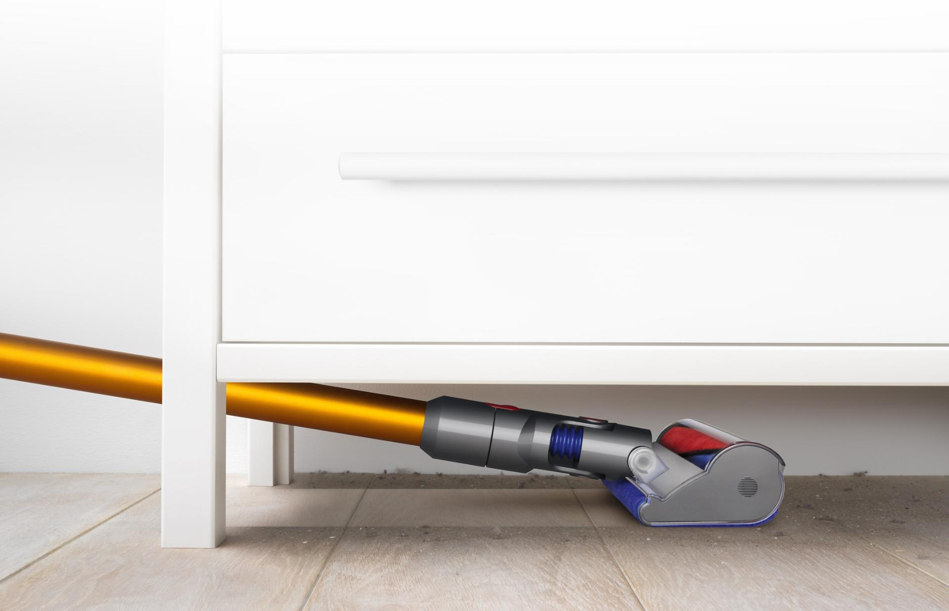 Dyson V8 vacuum cleaning hard floor under low positioned piece of furniture