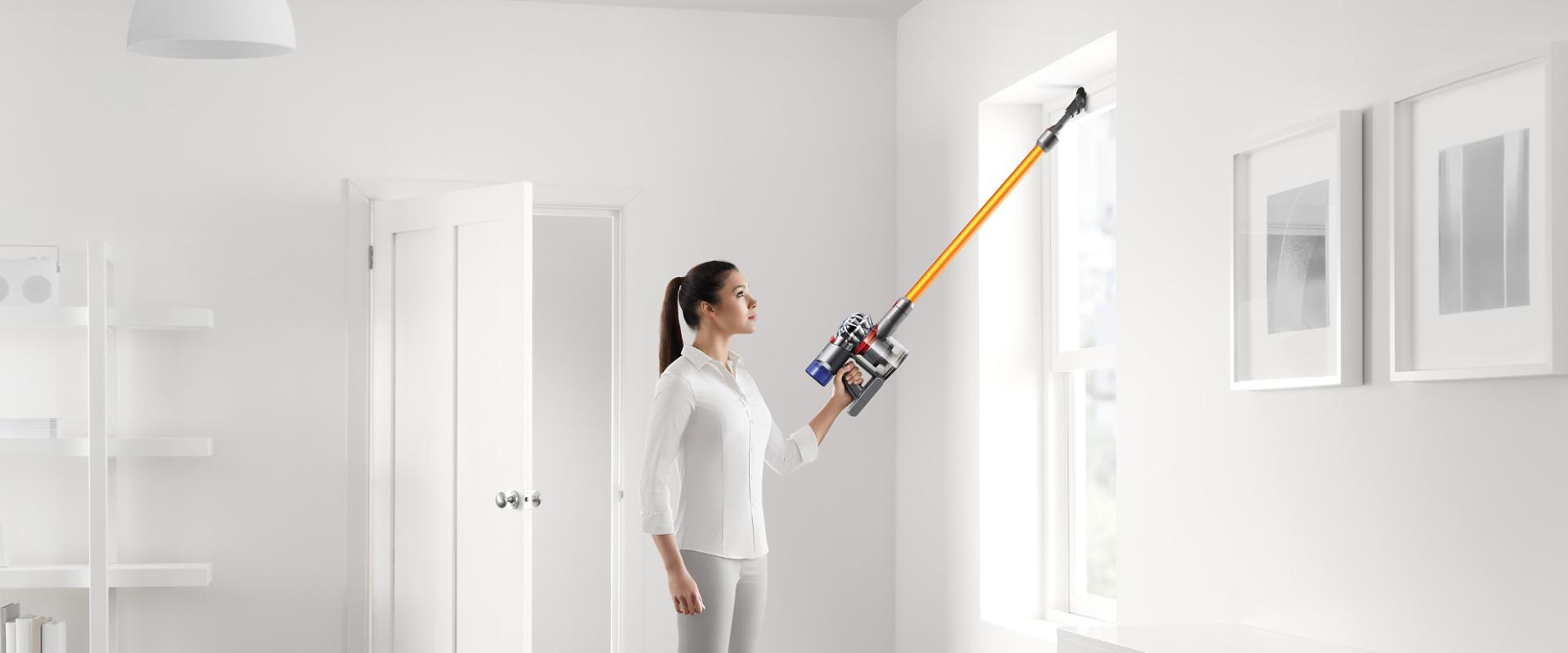 Woman using Dyson V8 to clean high position