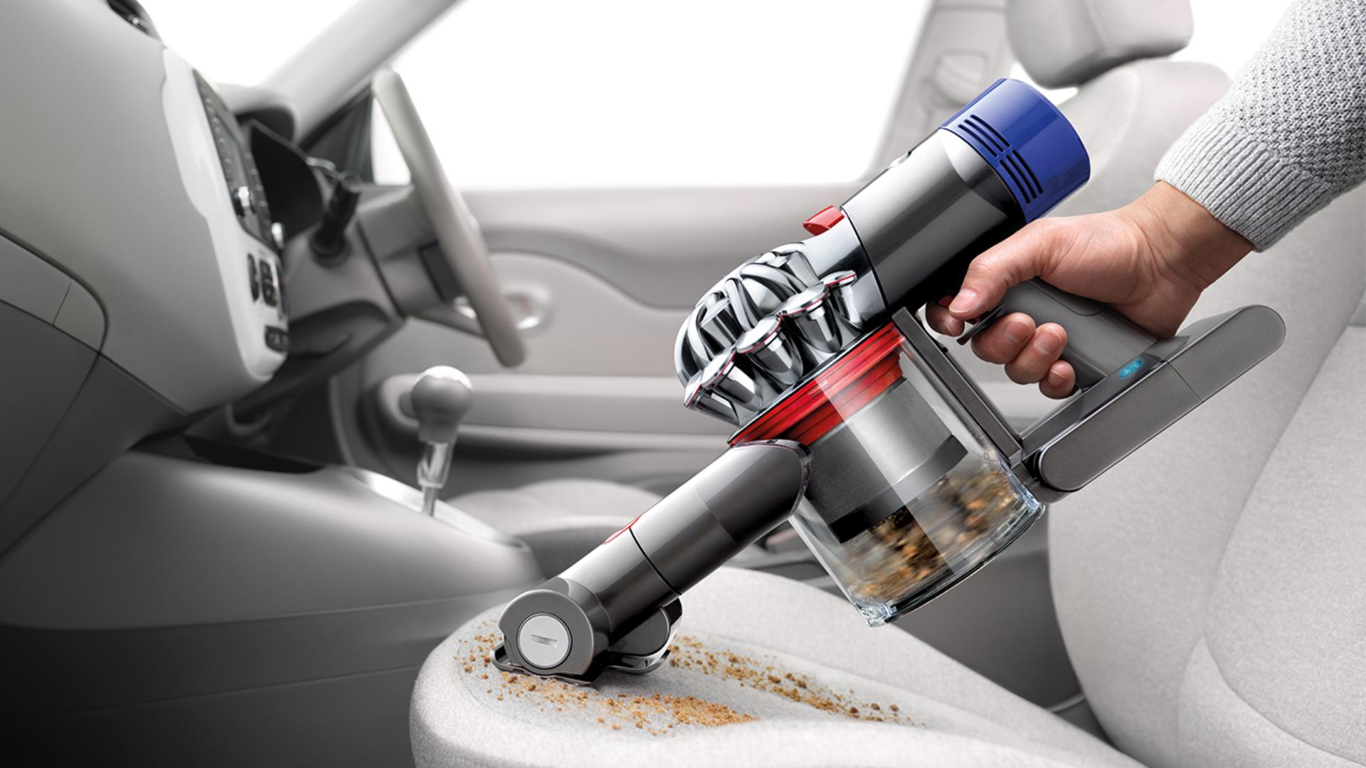 Dyson v8 cord-free vacuum cleaner being used as a handheld to clean car interior.