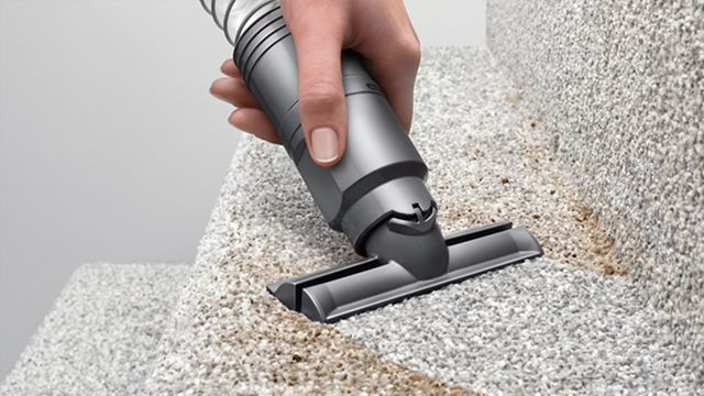 Vacuum cleaner stair tool being used on dirty staircase