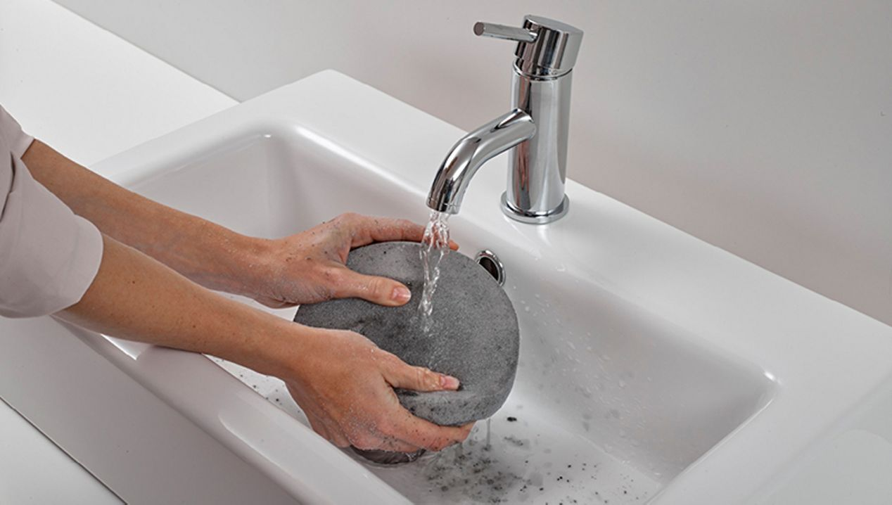 Filter being washed under a tap