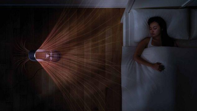 Femme dans son lit à côté du ventilateur chauffage DysonHot+Cool
