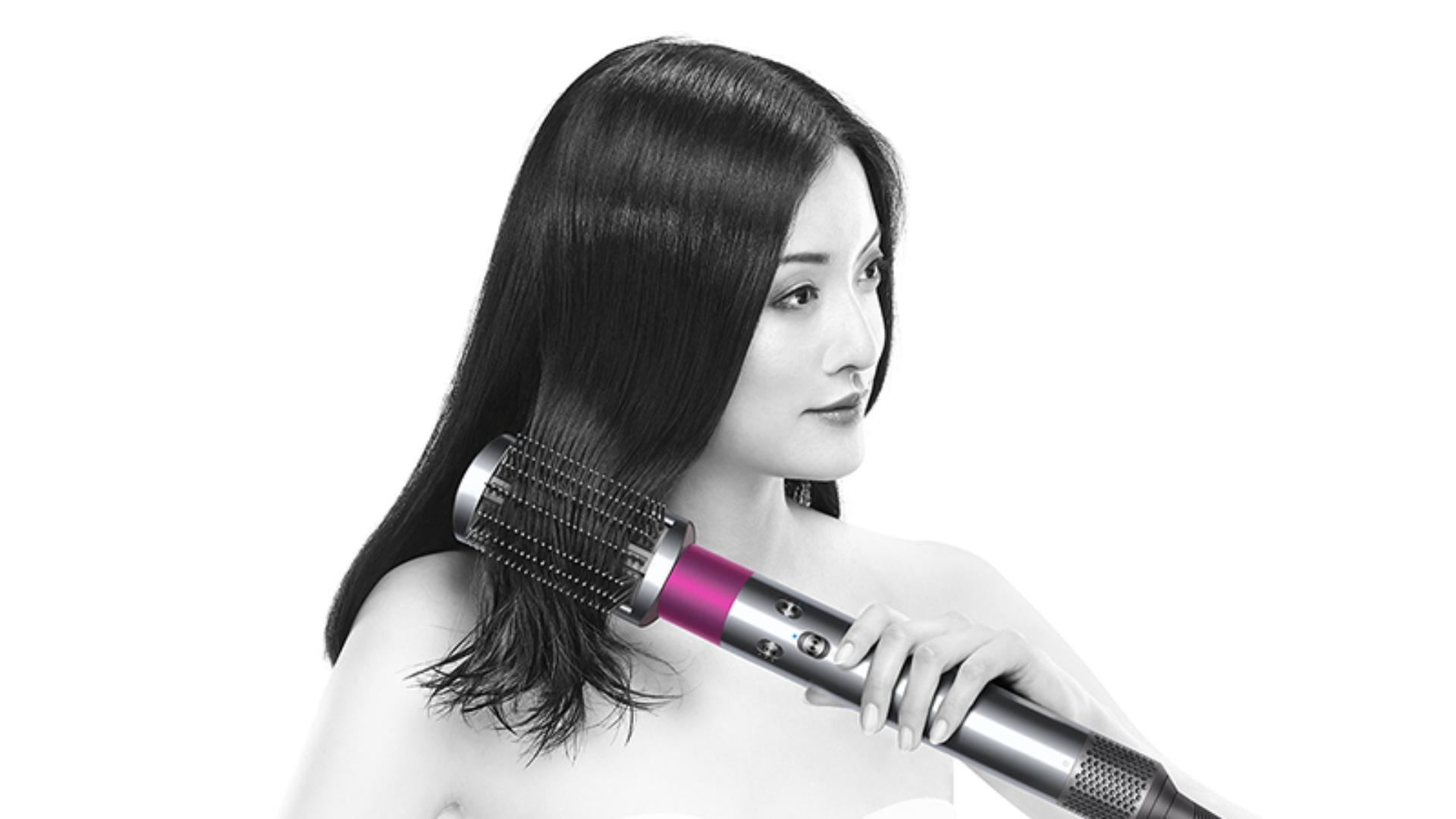 Model using The Dyson Airwrap™ to smooth frizzy hair