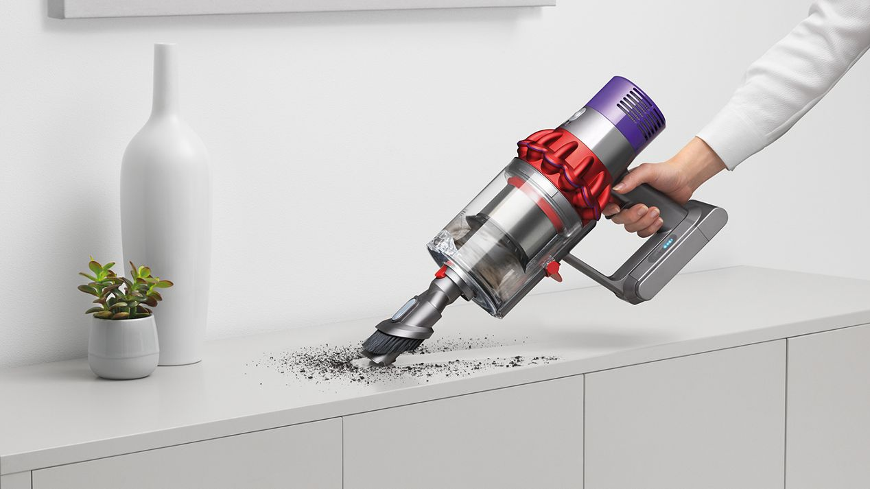 Dyson Cyclone V10™ vacuum in handheld mode cleaning furniture