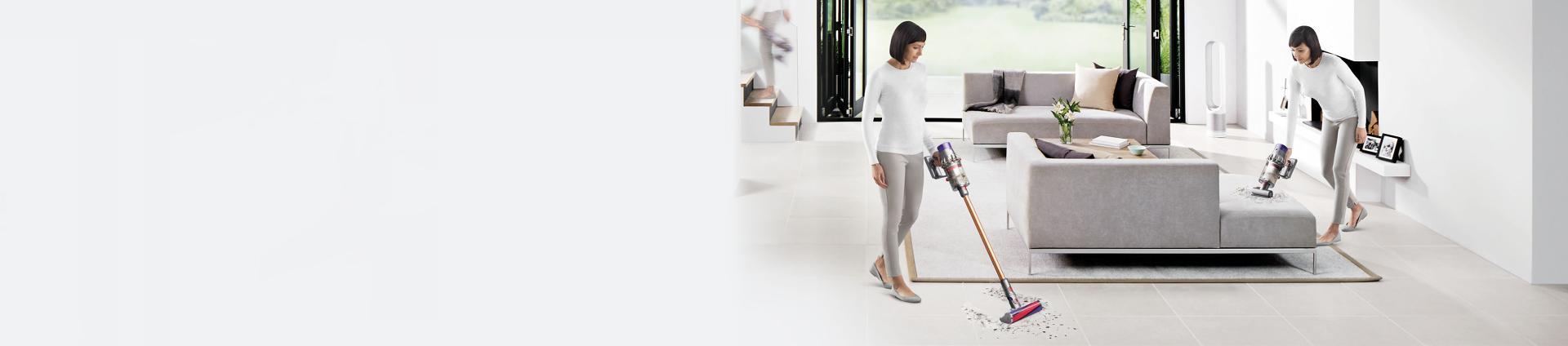 Evi temizlemek için Dyson Cyclone V10™ elektrikli süpürgeyi kullanan kadın