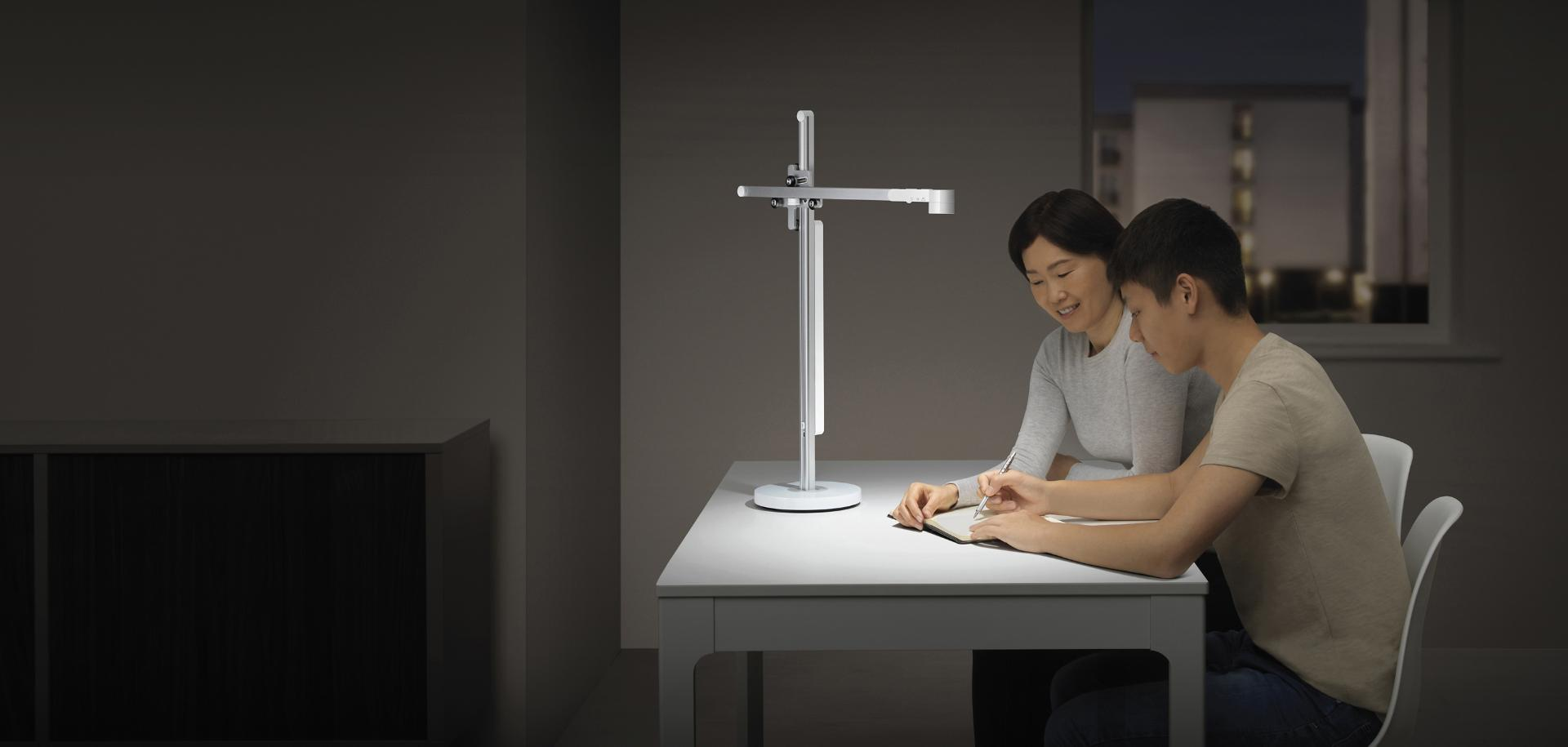 Mother and teenager studying under the Dyson Lightcycle task light