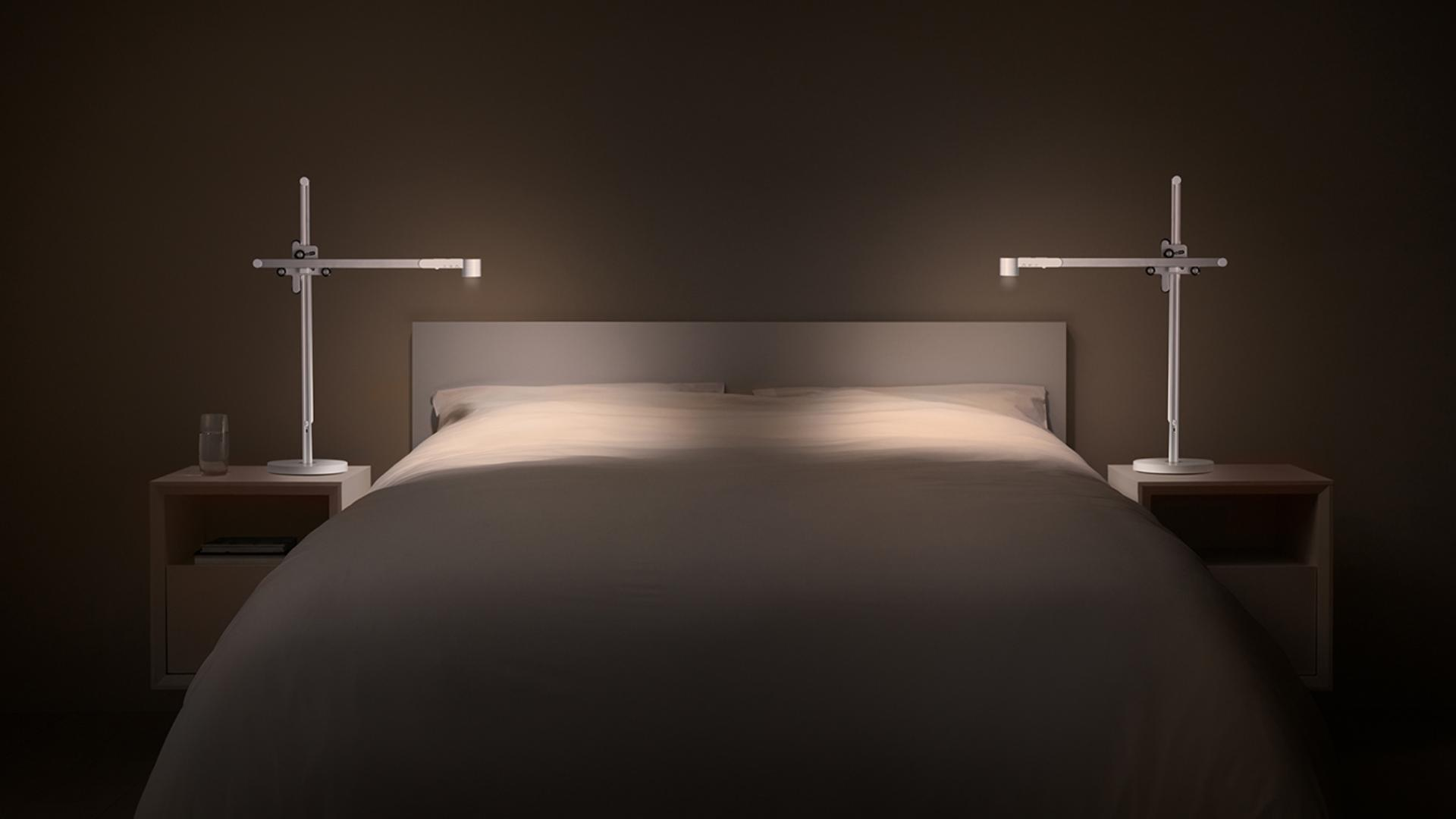Two Dyson Lightcycle™ task lights on either side of a bed in perfect symmetry