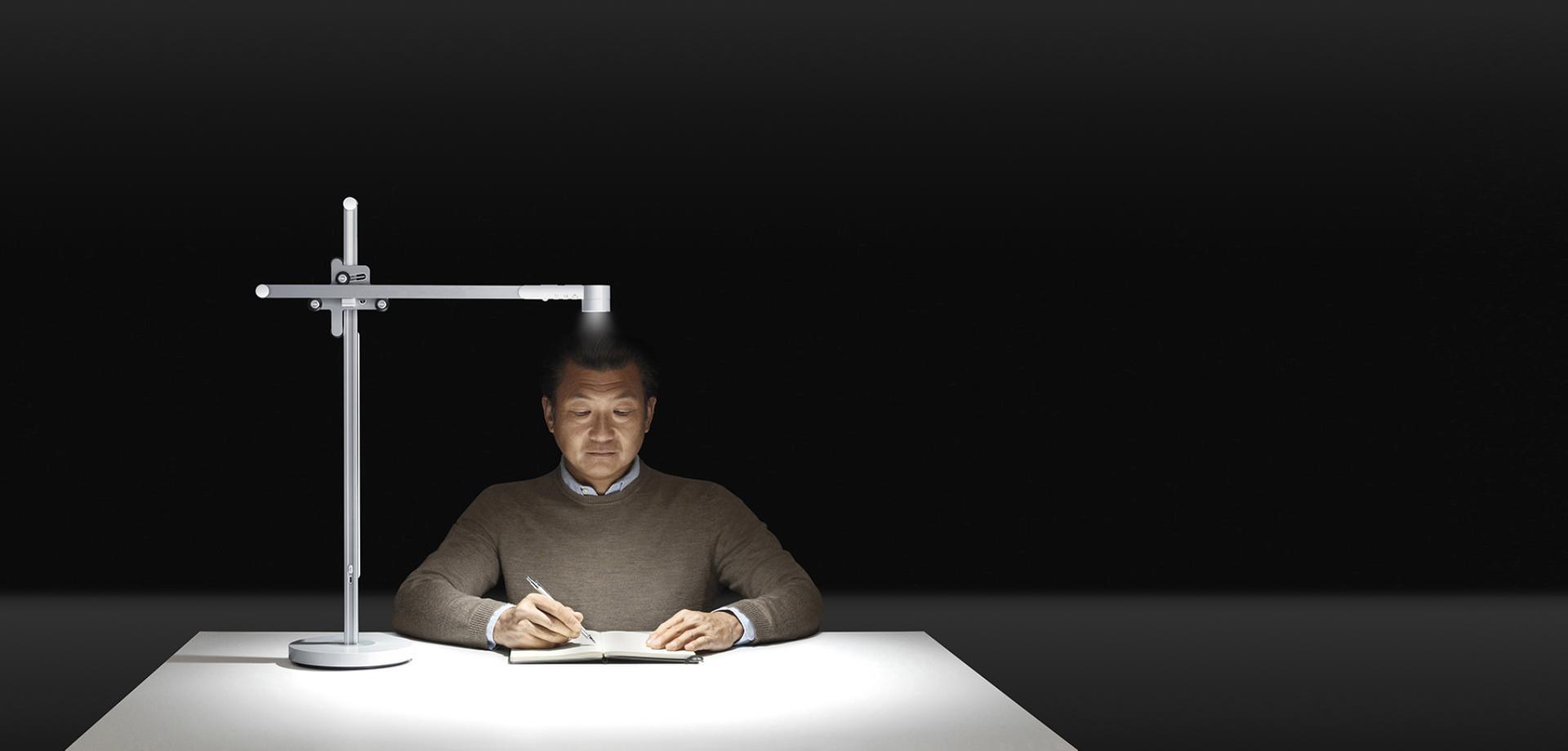 一位中年男士在建議亮度的燈光下閱讀