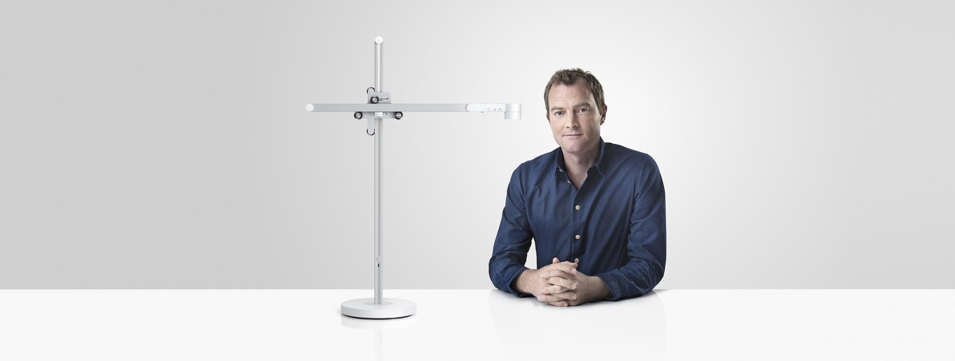 Jake Dyson sitting next to the Dyson Lightcycle™ task light