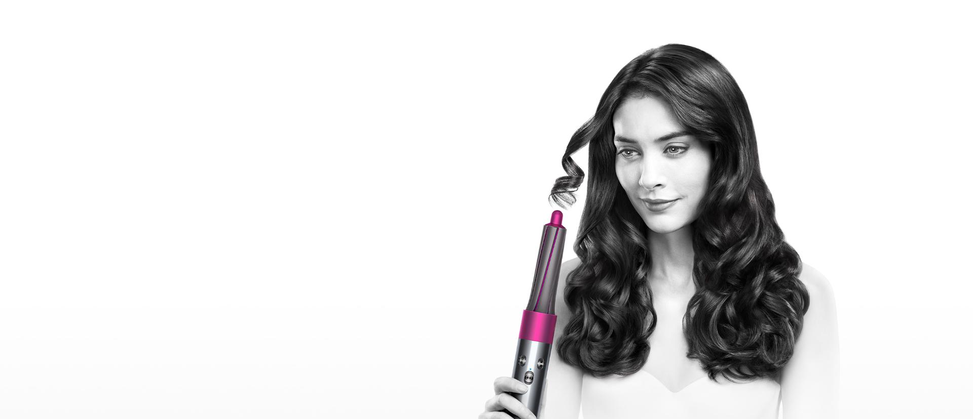 Model demonstrating the Dyson Airwrap™ hair styler to create bouncy curls