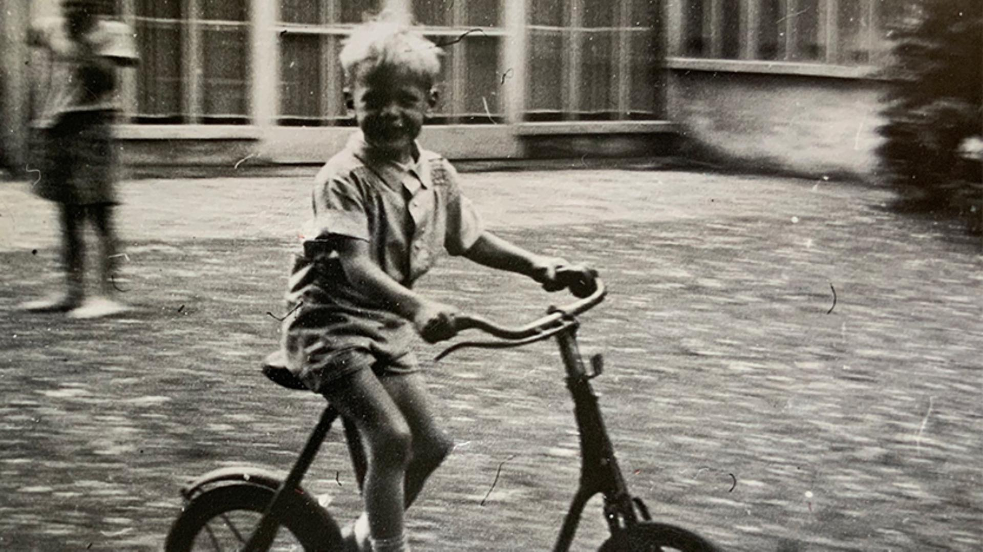Young James Dyson cycling a small Triang bike