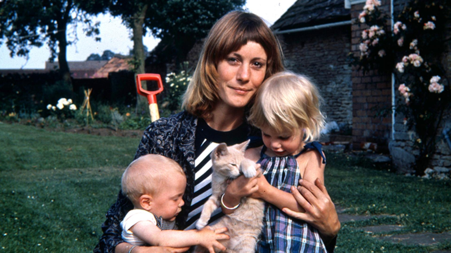 Deirdre Dyson holding toddler Emily, a young baby Jake, and a pet cat
