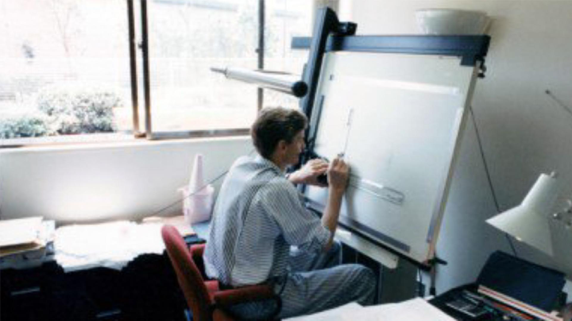 James Dyson seated in front of a technical drawing board