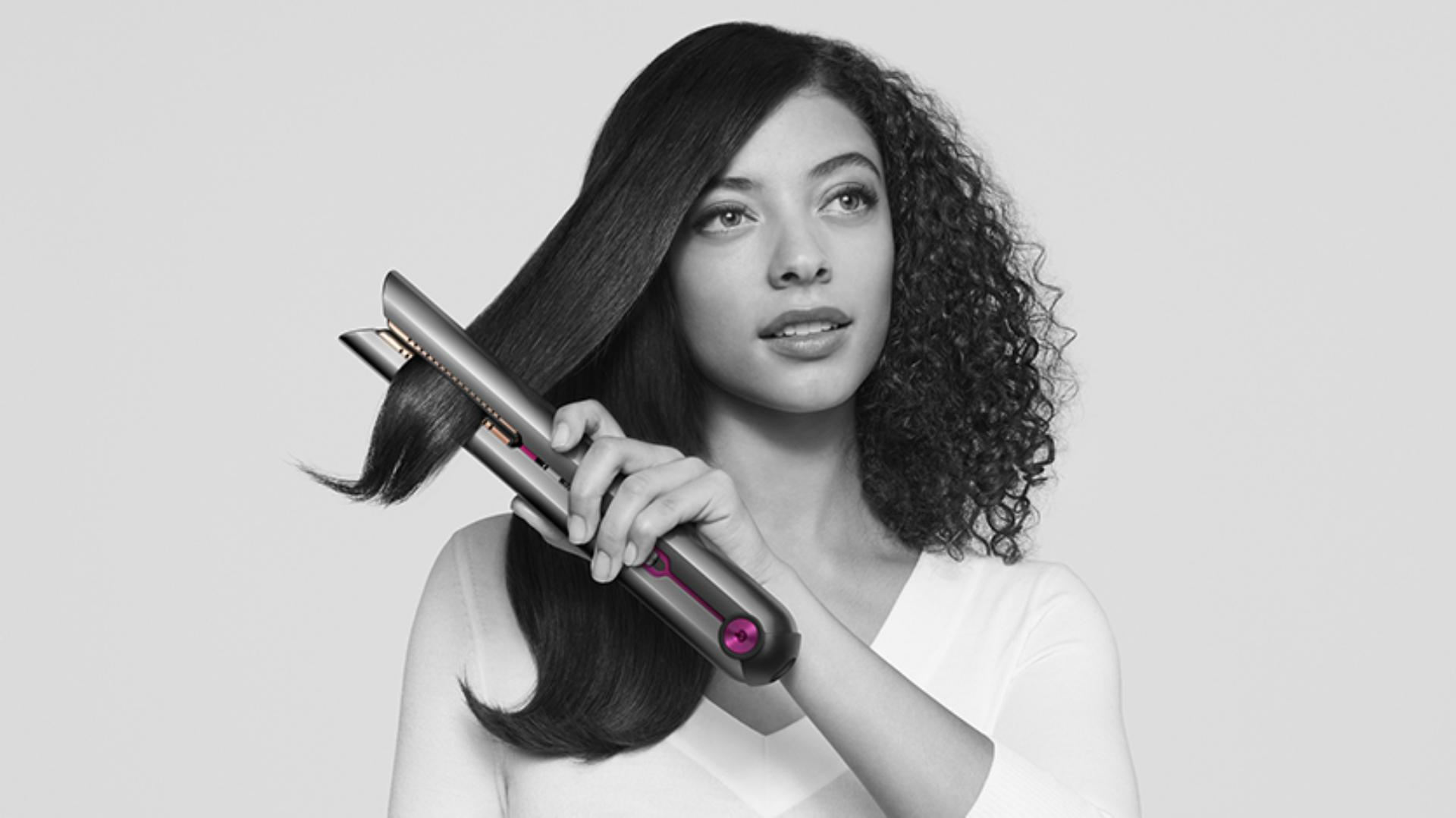 Female model holding the Dyson Corrale straightener in one hand