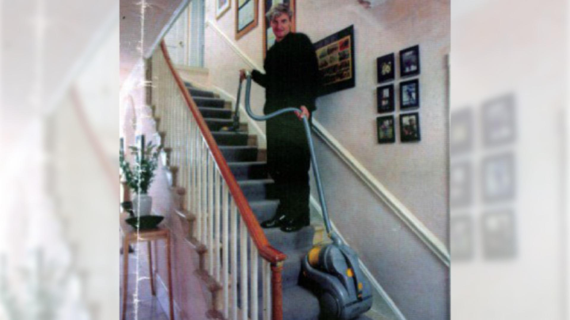 James Dyson standing halfway up the stairs, using the DC02 vacuum with ease