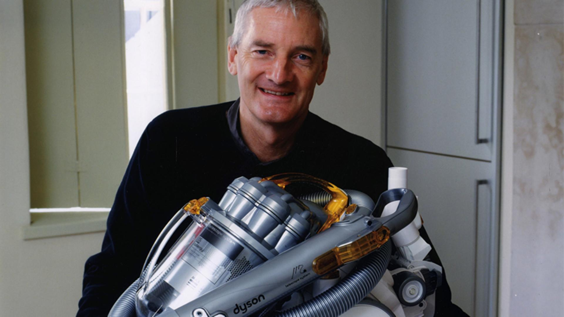 James Dyson sitting with a DC08 vacuum
