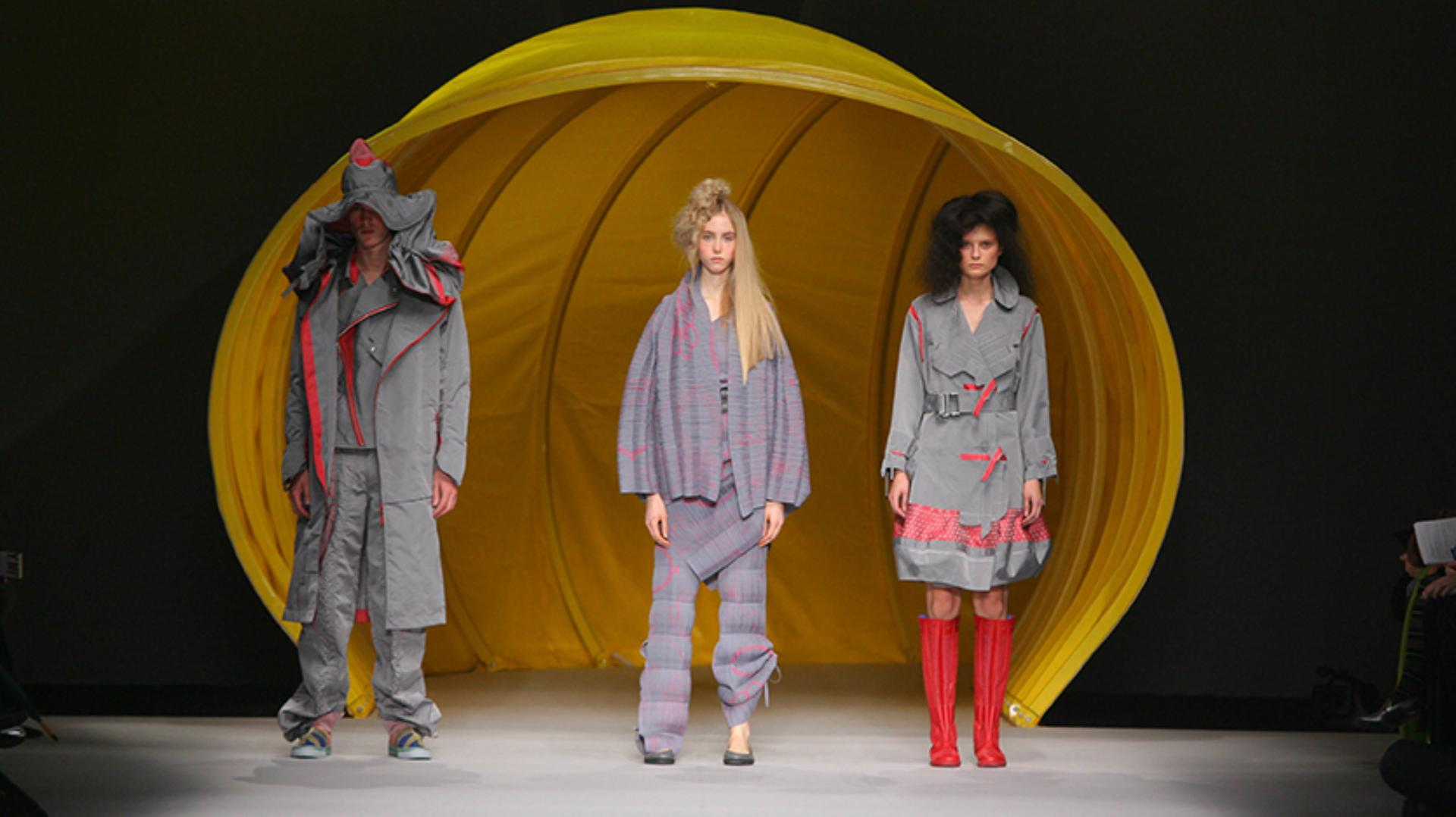 Models emerging from a giant yellow hose in Dyson vacuum-inspired designs onto the runaway