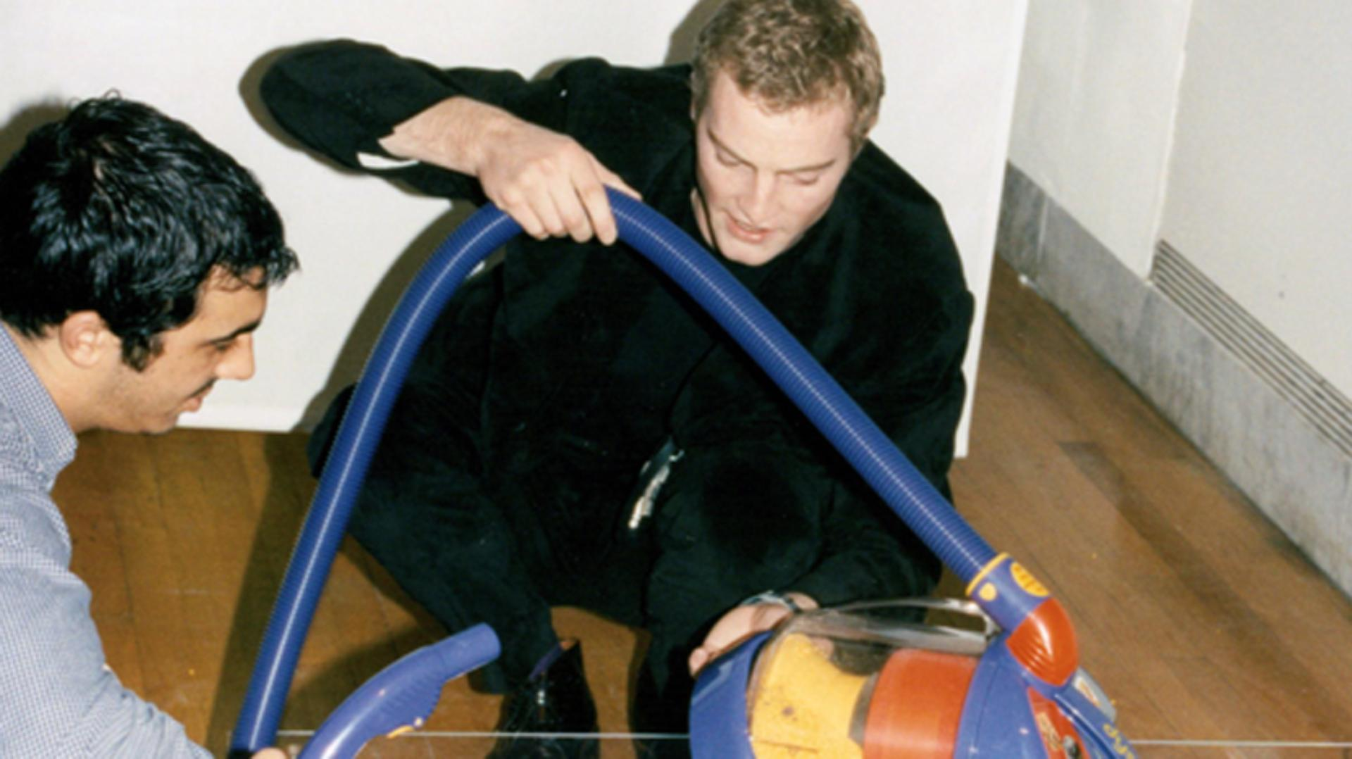 Jake Dyson crouched demonstrating a colourful DC02 vacuum at the Design Museum