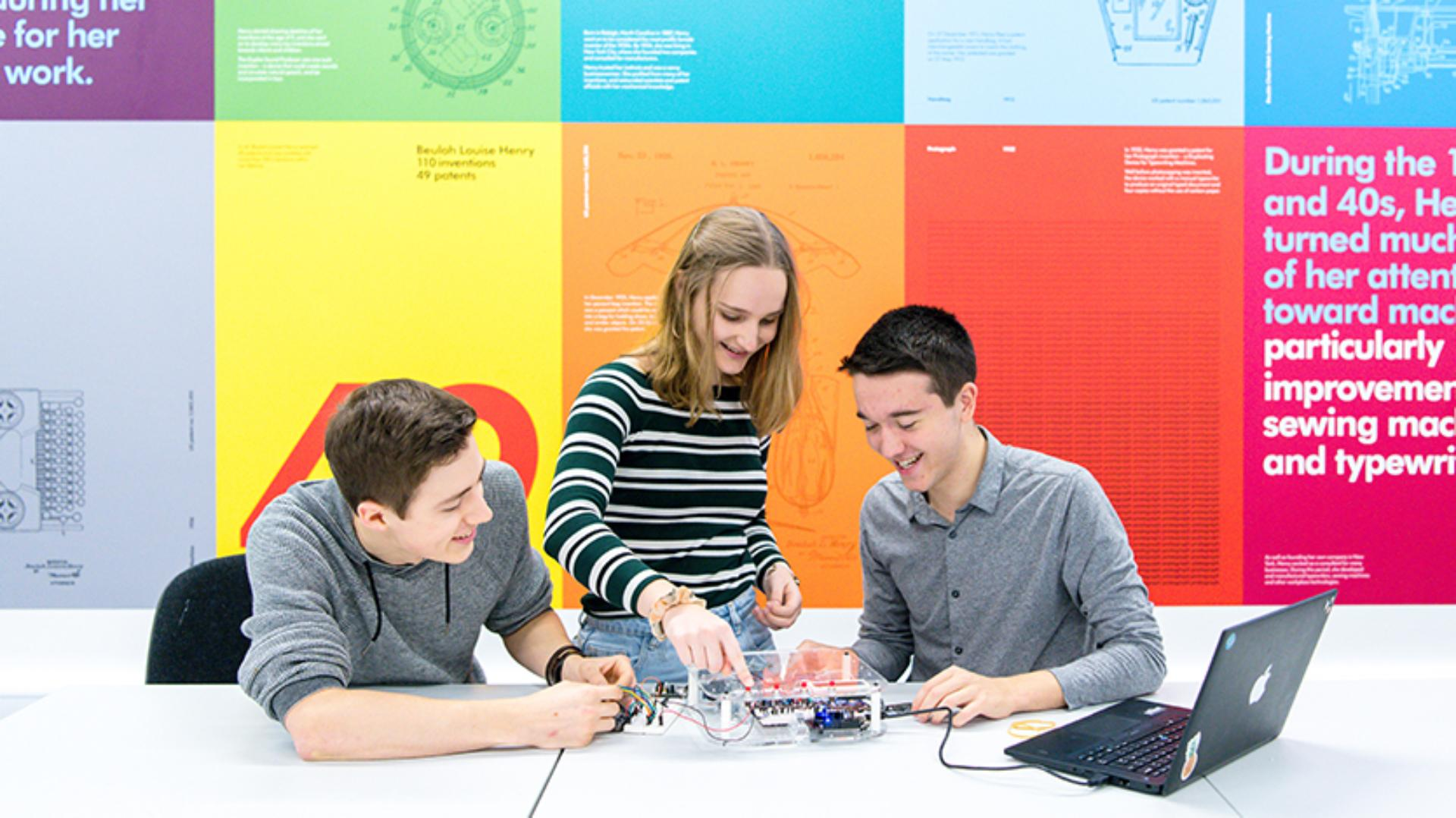 Three students learning whilst working on a project together