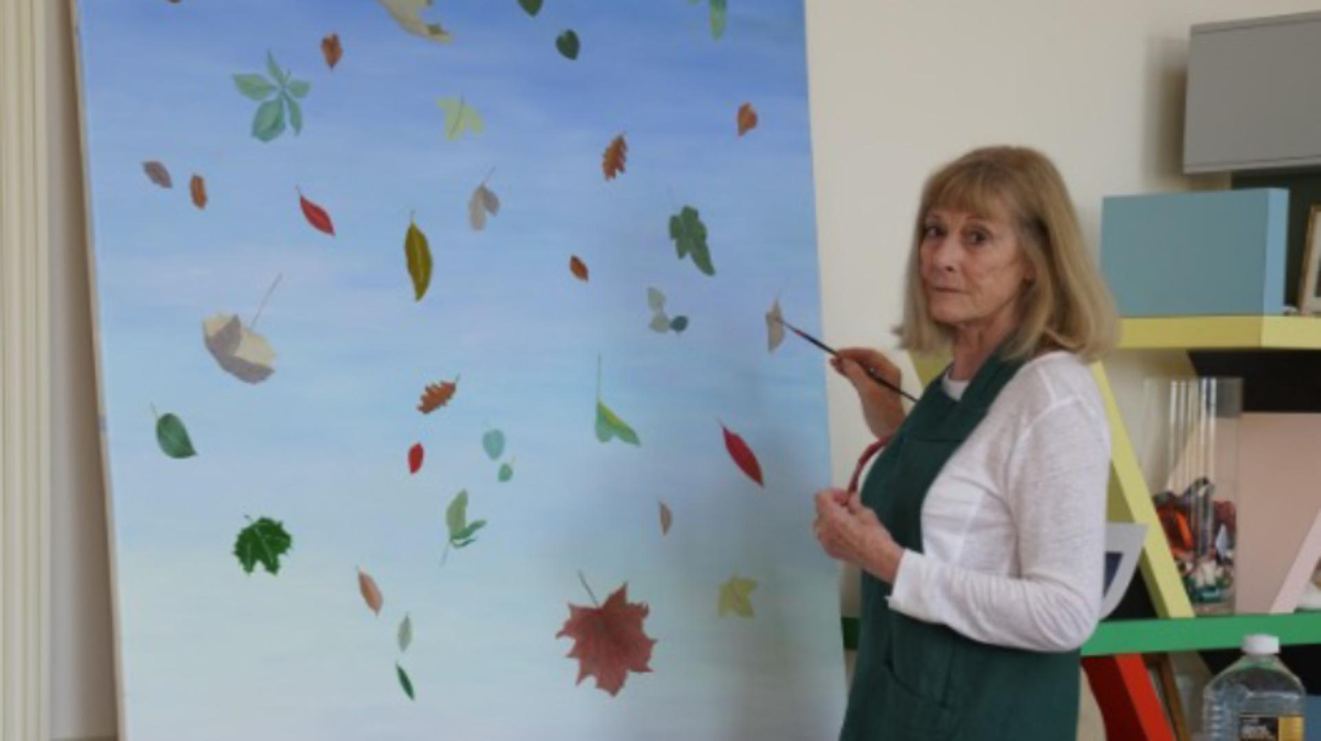 Deirdre Dyson painting falling leaves on a large canvas