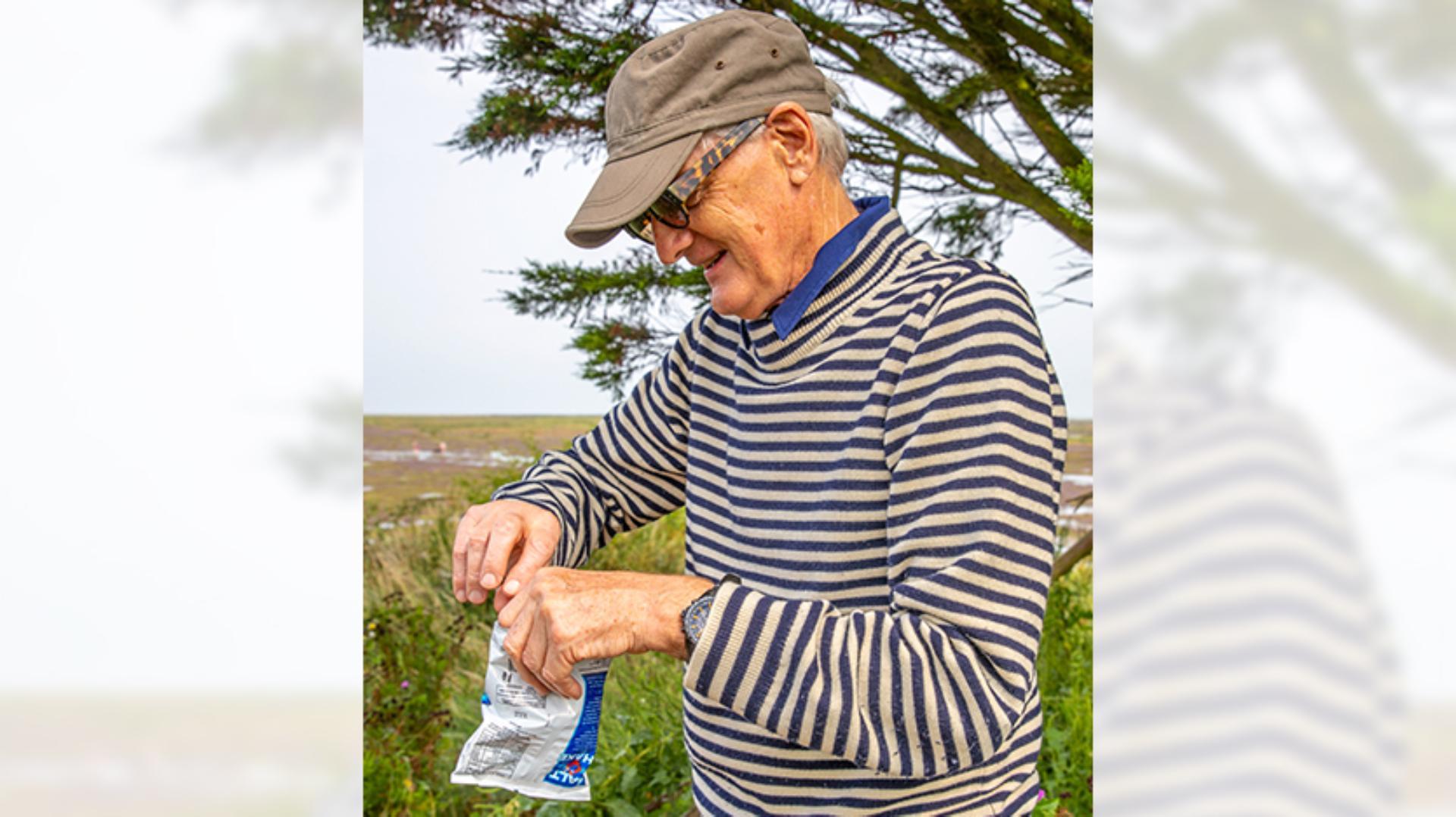 James Dyson holding a bag of Smiths potato crisps