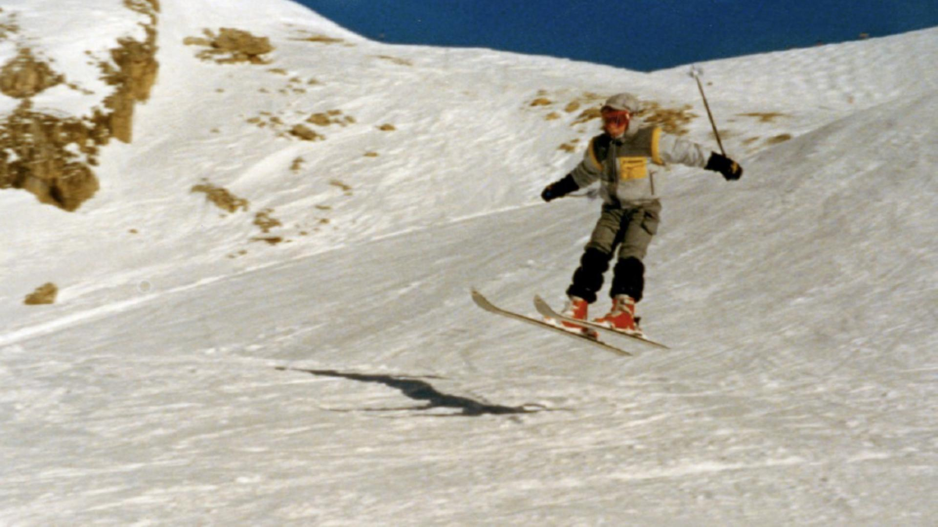 A young Dyson boy on a ski slope, making a jump, with ski poles in the air