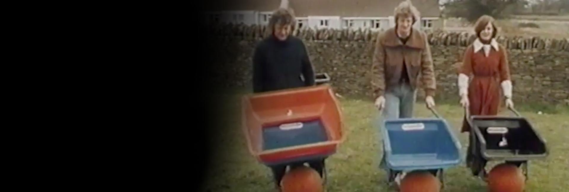James and Deirdre Dyson pushing Ballbarrows around a garden