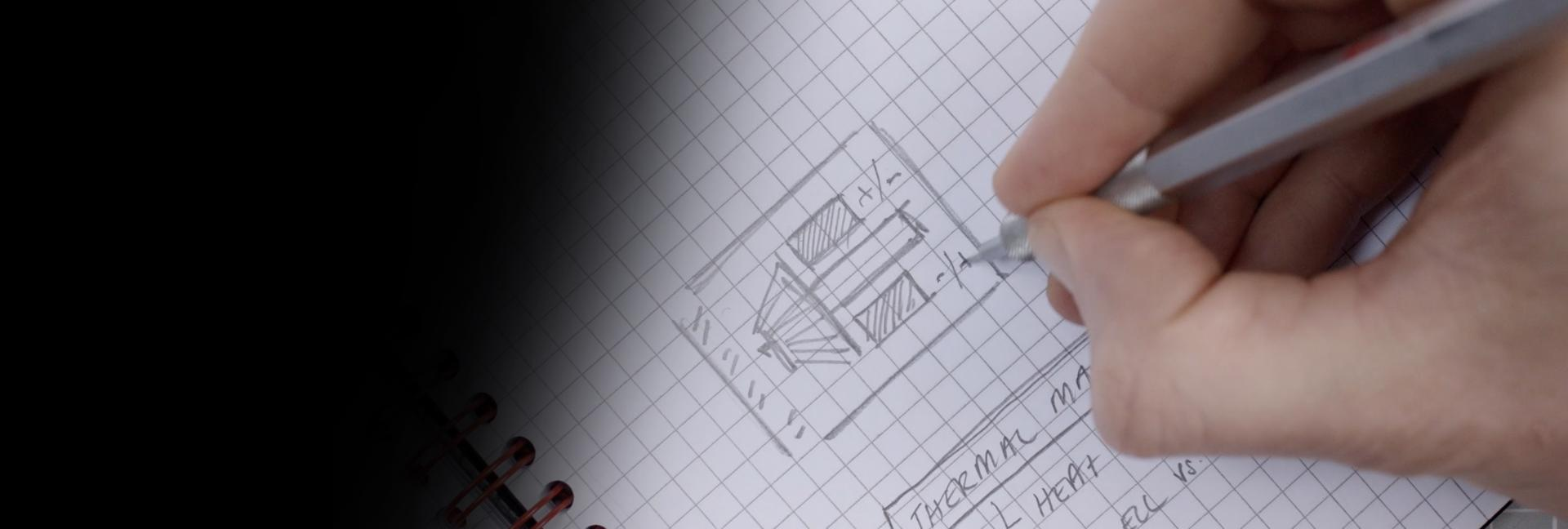 Close-up of James Dyson sketching on paper