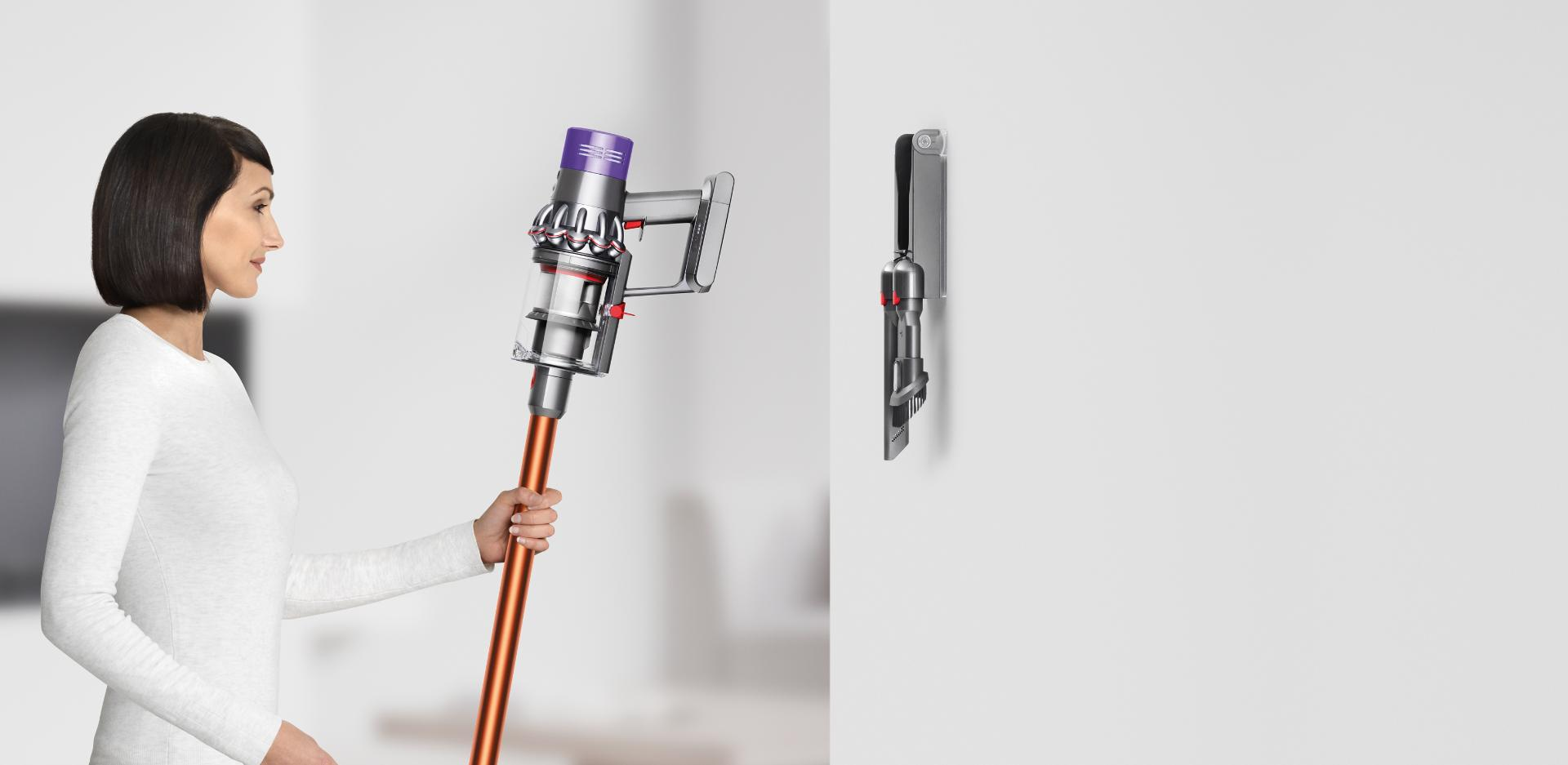 Woman placing Dyson Cyclone V10™ vacuum into wall dock